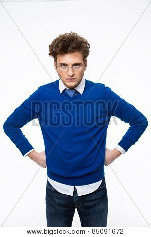 Dissatisfied young businessman in glasses looking at camera