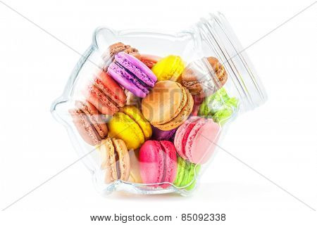 traditional french colorful macarons in a glass jar on white background