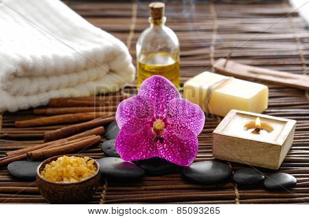 Spa resort -candle with gorgeous orchid ,salt in bowl and pebbles ,oil on mat