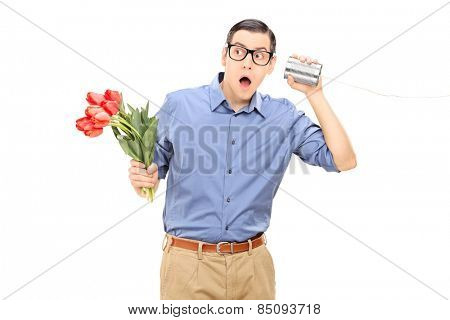 Young man holding flowers and listening through a tin can phone isolated on white background