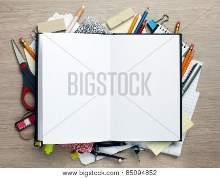 Open book with office supplies