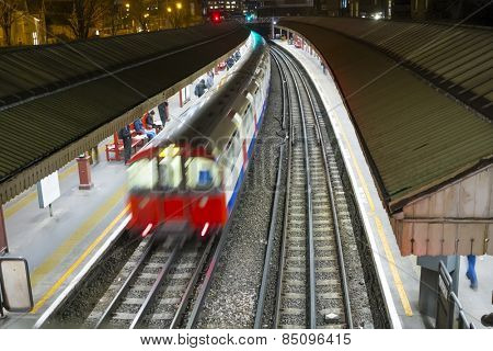 LONDON, UK - FEBRUARY 04: High angle motion blurred shot of Underground train in Baron's Court station. February 04, 2015 in London.