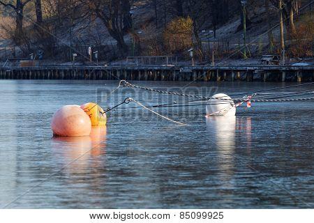 Three Buoys Reflecting In Ice