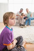 pic of sad boy  - Sad boy sitting on floor while parents enjoying with sister on sofa at home - JPG