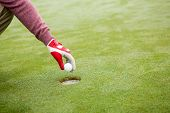 stock photo of cheater  - Golfer trying to flick ball into hole at the golf course - JPG