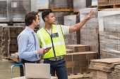 stock photo of warehouse  - Warehouse worker showing something to his manager in a large warehouse - JPG