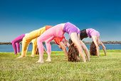 stock photo of suny  - People practice Yoga asana at lakeside on suny day - JPG
