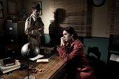 stock photo of crime scene  - Detective interviewing a young sad woman in his office film noir scene - JPG