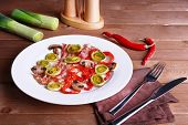 pic of bacon strips  - Strips of bacon with sliced shallot and pepper in plate on wooden table background - JPG