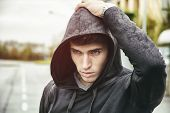 picture of hoodie  - Handsome young man in black hoodie sweater standing outdoor in street hand over his head