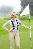 pic of ladies golf  - Lady golfer holding flag on a foggy day at the golf course - JPG
