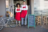 image of apron  - Smiling colleagues in red apron with arms crossed at the bakery - JPG