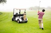 foto of buggy  - Golfer teeing off next to his golf buggy at the golf course - JPG