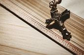stock photo of crucifix  - Open bible and silver crucifix on wooden table - JPG