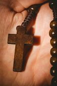 stock photo of rosary  - Hand holding wooden rosary beads in close up - JPG
