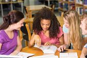 stock photo of homework  - Group of college students doing homework in the library - JPG