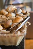 stock photo of tong  - Basket with fresh bread and tongs at the bakery - JPG