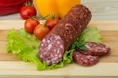 foto of salami  - Sliced Salami with salad leaves on the wood background - JPG