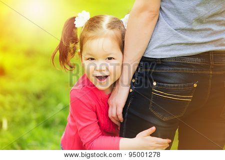 Little Girl Cheerfully Hugging Leg Of Mother