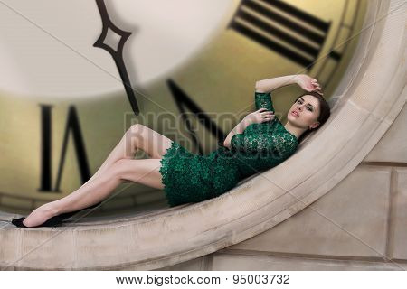 girl in a long dress with plume lying on the floor on her dress near the huge clock