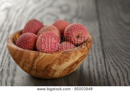 ripe lychees in wood bowl on table