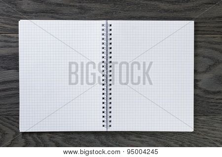blank notepad with chequered pages on gray wood table