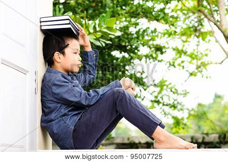 Young Boy Put The Books On His Head
