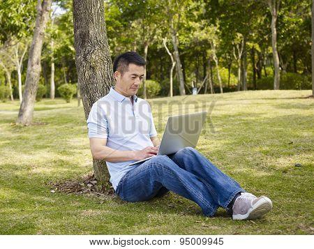 Asian Man Using Laptop Outdoors