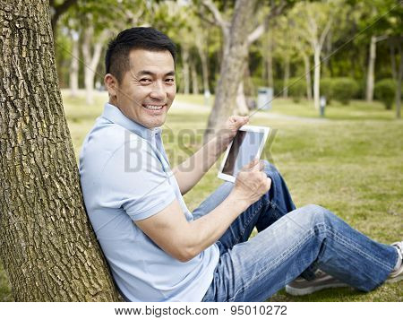 Asian Man Using Tablet Outdoors