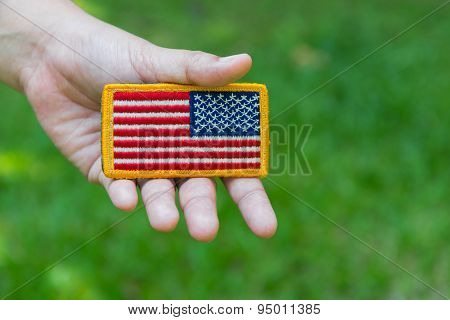 Hand holding Rounded American flag patch