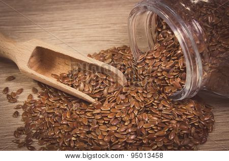 Vintage Photo Of Linseed Spilling Out Of Jar On Wooden Background