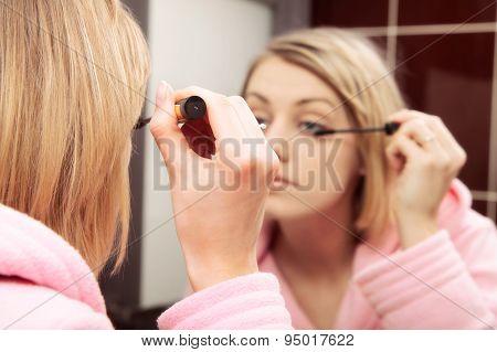 Woman applying mascara on eyelashe