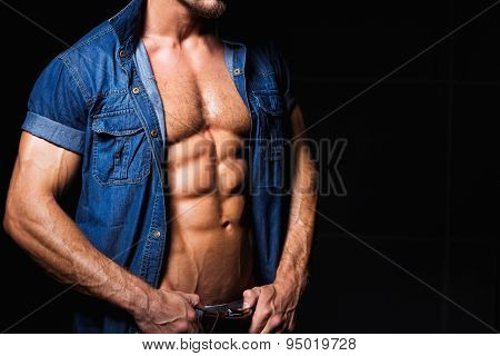 Muscular and sexy young man in jeans shirt with perfect body