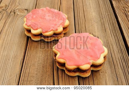 Two Double Round Sand Cakes Decorated With Pink Icing And Jam On Rustic Table