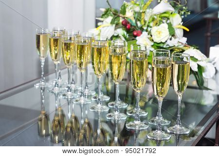 Elegant glasses with champagne standing in a row