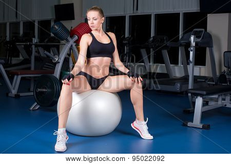Pilates instructor starting exercise sitting on fitness ball. Sport woman working out in gym