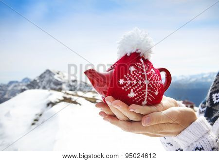 Tea Pot In The Knotted Cap In The Hands