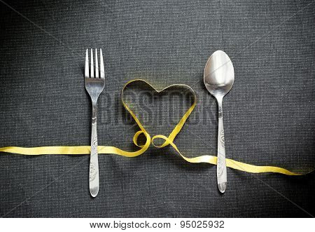 Fork And Spoon With Heart Shape Made From Yellow Ribbon On Black Textured Background
