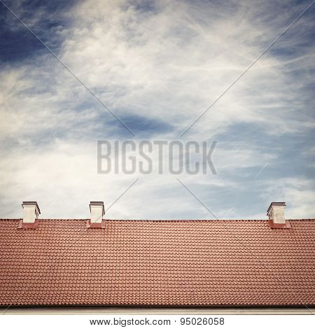cloudy blue sky and tiled roof top