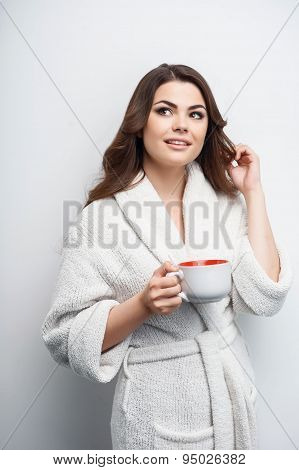 Pretty young woman is holding cup with enjoyment