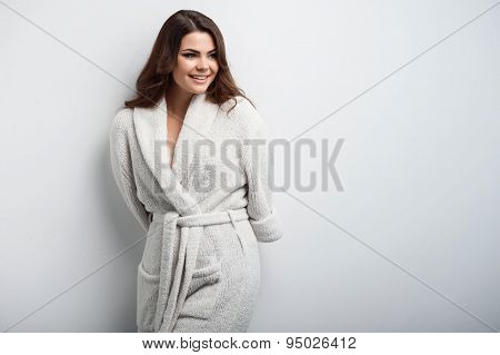 Cheerful young woman is in white bathrobe