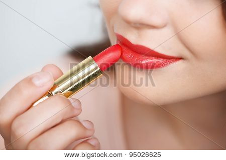 Cheerful young girl is doing her make-up