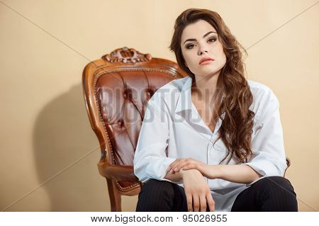Beautiful young woman is situated on chair
