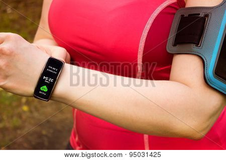 Sporty Woman Using Smart Watch. Interface On Watch Screen Was Generated In Graphical Program