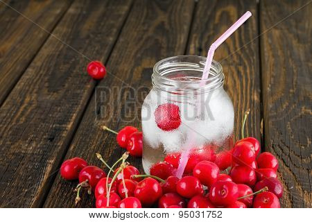 Wet Glass Jar Full Of Ice Cubes And Cherries