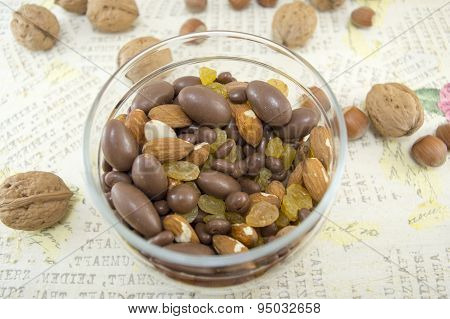 Mix Of Nuts, Raisins,hazelnuts, Almonds And Chocolate In The Bowl On  A Decoupage Decorated Table