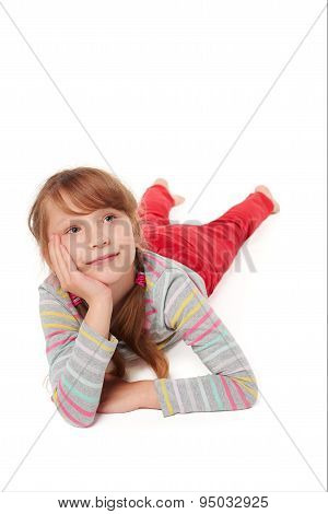 Front view of smiling child girl lying on floor