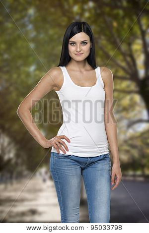 Close Up Of The Brunette Lady In A Tank Top. A Park With Trees As A Background
