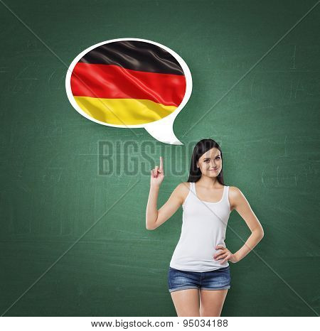 Beautiful Woman Is Pointing Out The Thought Bubble With German Flag. Green Chalk Board Background.
