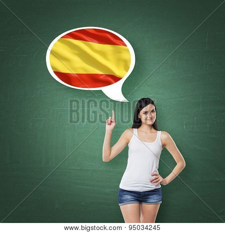 Beautiful Woman Is Pointing Out The Thought Bubble With Spanish Flag. Green Chalk Board Background.